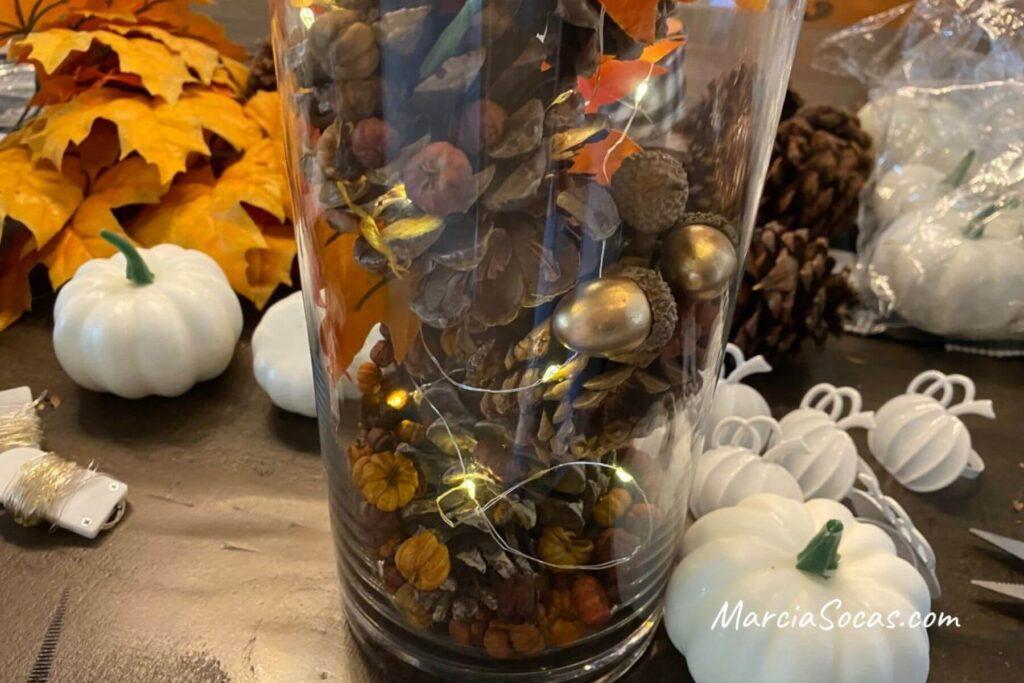 vase with fairy lights, pine cones, acorns, and potpourri