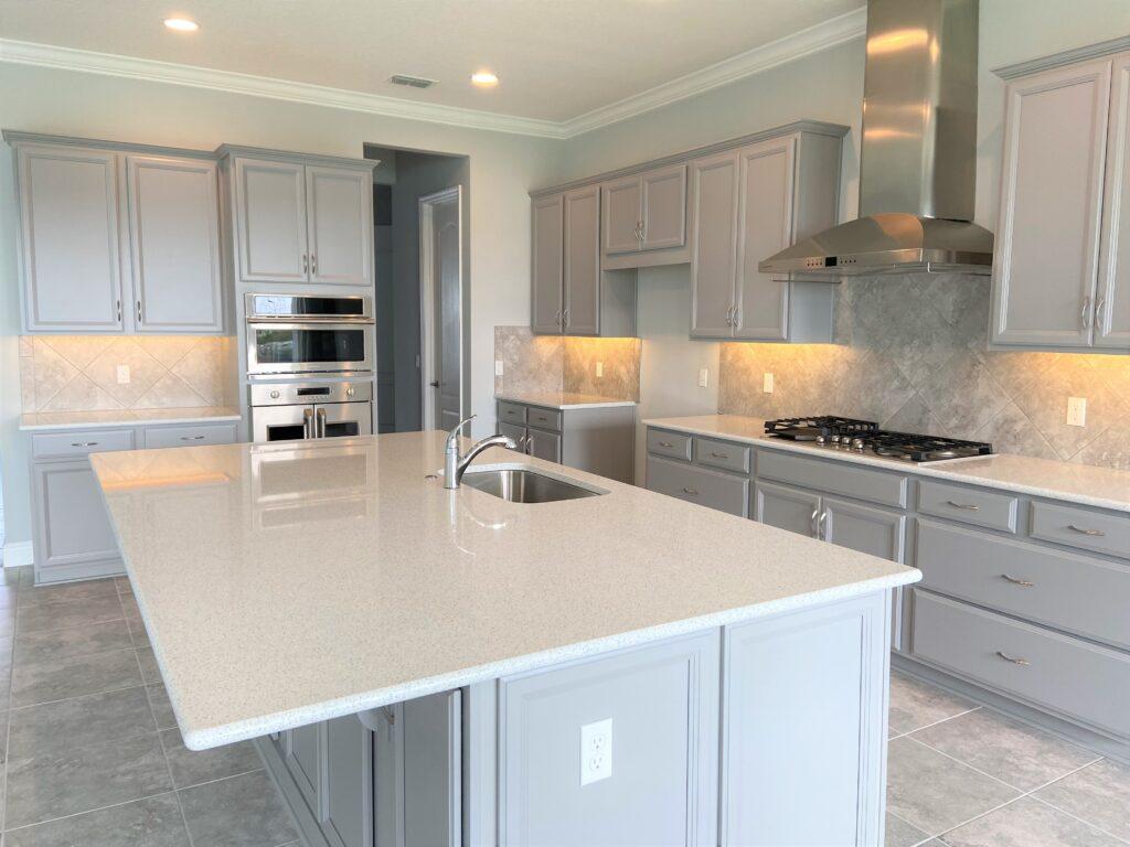 Large white quartz island and gray cabinets