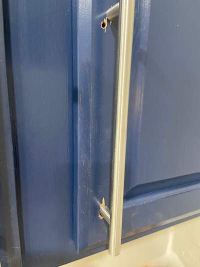 Holes and splintering in the cabinet door