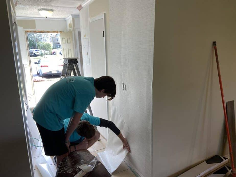 kids installing wallpaper entryway