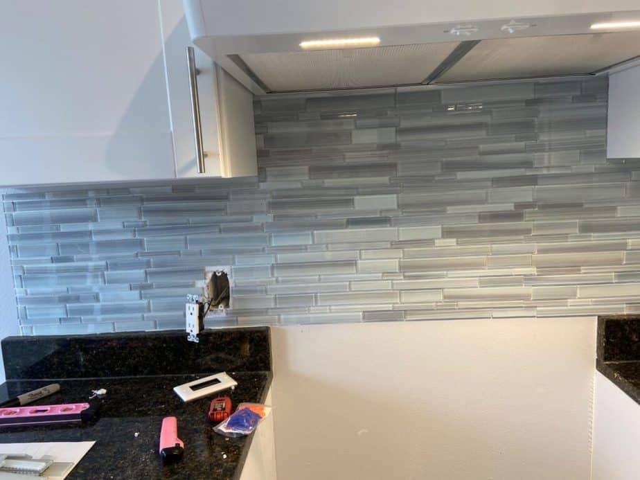 blue glass staggered tile backsplash before grouting