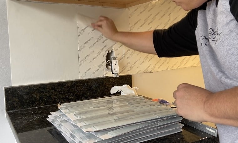 Peeling cover off of adhesive mat